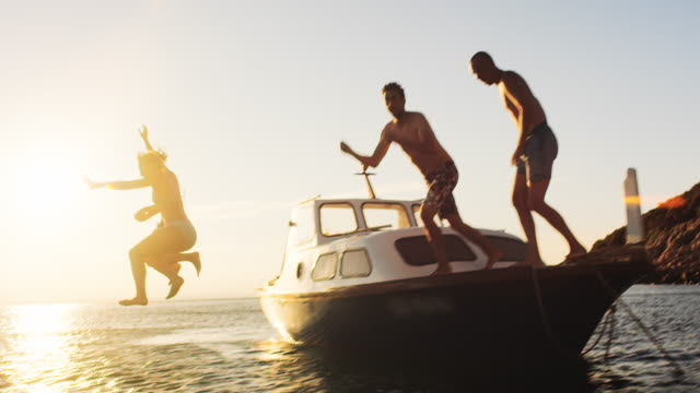 slo mo people jumping off the boat in sunset - nautical vessel stock videos & royalty-free footage