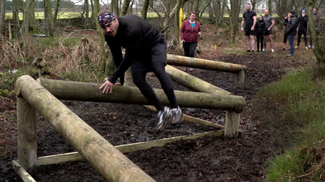 people jumping over logs in assault course / obstacle course - slow motion - crawling stock videos and b-roll footage