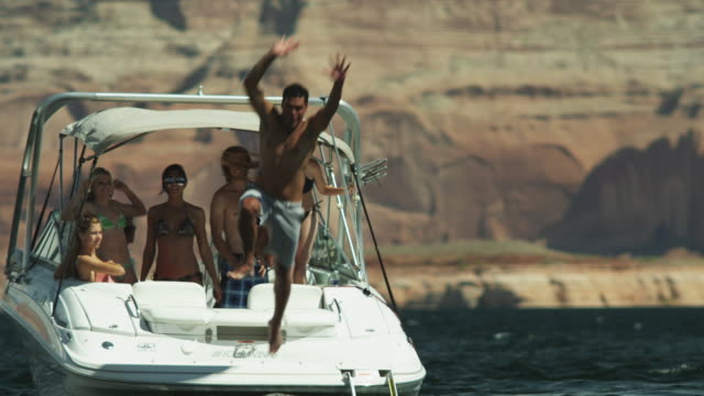 vídeos de stock e filmes b-roll de slo mo ws people jumping to lake powell from boat / utah, usa - lago powell