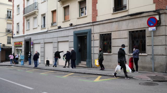 people keep their distance as they wait their turn in a queue to access a ahorra mas supermarket during the coronavirus pandemic on april 11 2020 in... - questioni sociali video stock e b–roll