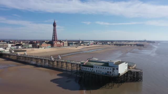 people keep their social distance on a deserted blackpool beach on march 22, 2020 in blackpool, england. many of the uk tourist areas have seen an... - absence stock videos & royalty-free footage