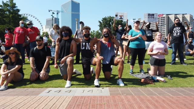 people kneel on one knee listening to a speaker during a juneteenth event organized by the one race movement on june 19, 2020 in atlanta, georgia.... - ひざまずく点の映像素材/bロール