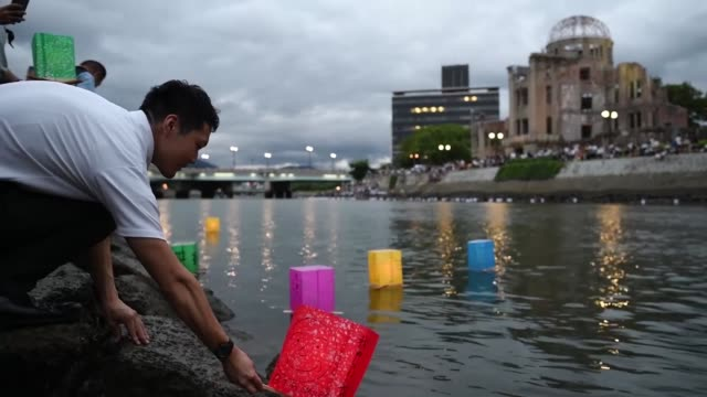 people launch lanterns for the hiroshima peace memorial ceremony and peace message lantern floating ceremony in hiroshima, japan to mark the 74th... - 核兵器点の映像素材/bロール