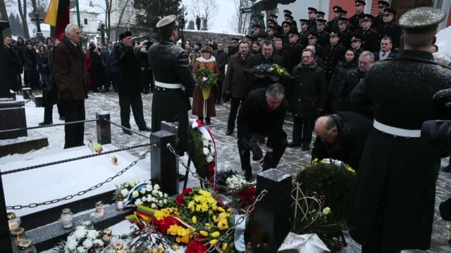 People lay candles and wreaths at the grave of Lithuanian National Revival activist Jonas Basanavicius during a state ceremony at Rasos Cemetery...
