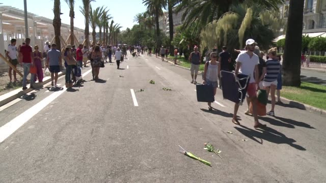 people lay flowers and came to reflect at the promenade des anglais as the beachfront road in the french resort of nice partially reopened to the... - promenade stock videos & royalty-free footage