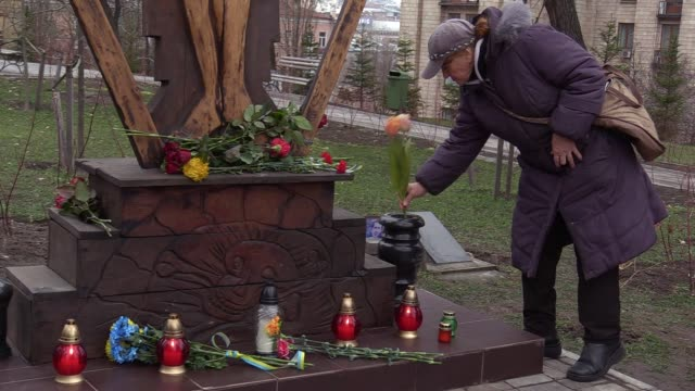 People lays flowers and light candles at the memorial for the killed Maidan activists during the third anniversary of the Euromaidan Revolution in...