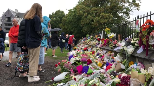 People leave messages and flowers for the victims of the Christchurch mosque attacks outside the Botanic Gardens on March 17 2019 in Christchurch New...