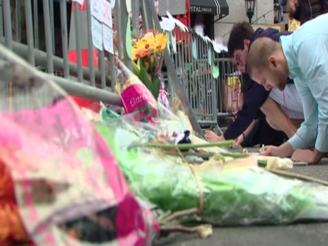People leave tributes to the victims of the Boston Marathon bombings