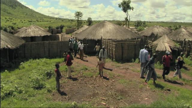 vídeos de stock e filmes b-roll de ws people leaving cluster of hut / mozambique - moçambique
