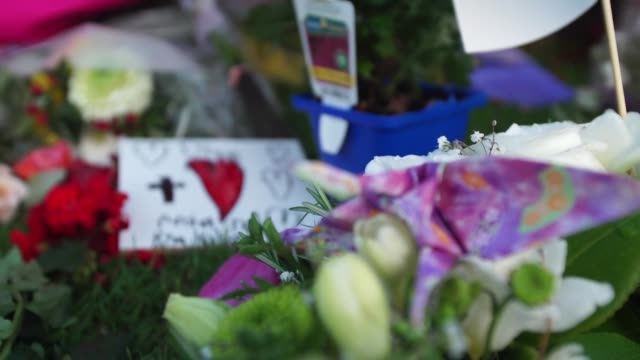 People leaving floral tributes after a white supremacist terrorist murdered 50 people at two mosques in Christchurch New Zealand