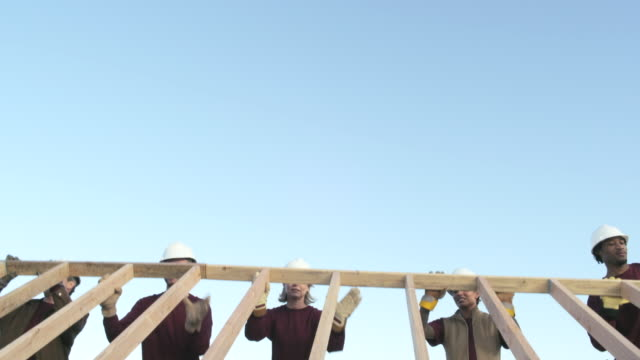 People lifting wooden construction frame