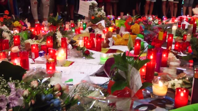 People light candles and leave flowers and notes at La Rambla boulevard for the victims those who lost their lives in terror attack killing at least...