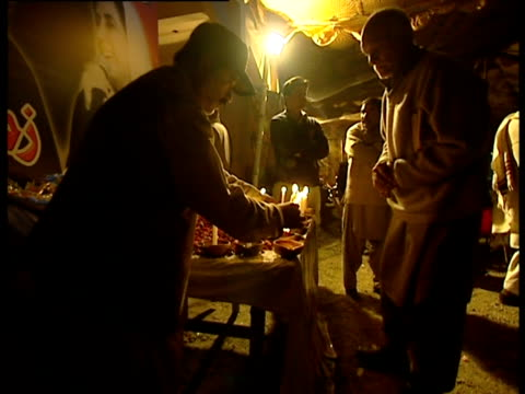 people light candles at memorial site for benazir bhutto following her assassination - 仮設追悼施設点の映像素材/bロール