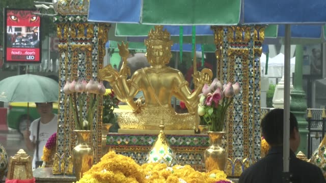 people light candles in the rain at erawan shrine in bangkok, thailand. erawan was the scene of a bombing which killed 20 people. - エラワン聖堂点の映像素材/bロール