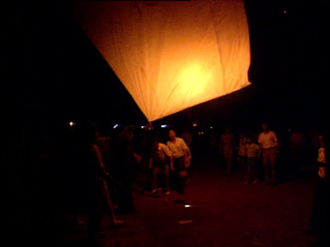 people lighting fire in basket beneath large orange paper balloon which rises into night sky fire crackers explode taiwan - taiwan stock videos & royalty-free footage