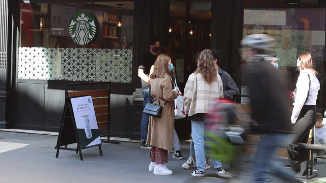 people line up in front of a starbucks café in paris - in a row stock videos & royalty-free footage