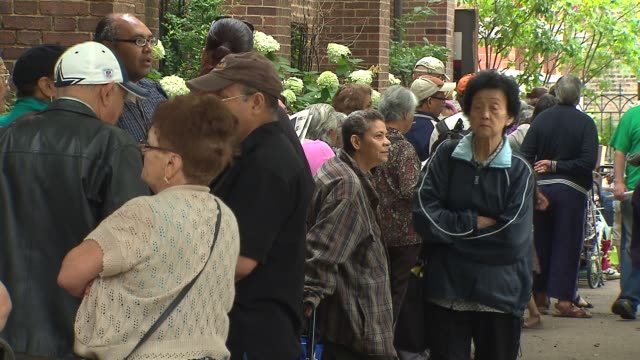 people line up outside of common pantry in the epiphany united church of christ on the corner of damen ave and bradley pl in chicago on aug 18 2014 - soup kitchen stock videos & royalty-free footage