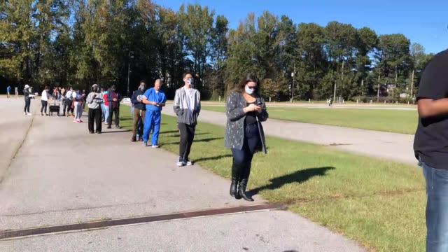 people line up to vote at the gwinnett county fairgrounds on october 30, 2020 in lawrenceville, georgia. hundreds of people lined up for about an... - in a row stock videos & royalty-free footage