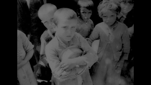vs people lined up at storefront policeman stands by in bakery old woman in babushka and children holding bread children with grain pouring through... - grain cart stock videos & royalty-free footage