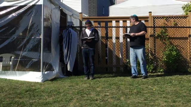 people listen as jewish men recite prayers inside a tent outdoors during the holiday of rosh hashanah during a special rosh hashanah celebration... - rosh hashanah stock videos & royalty-free footage