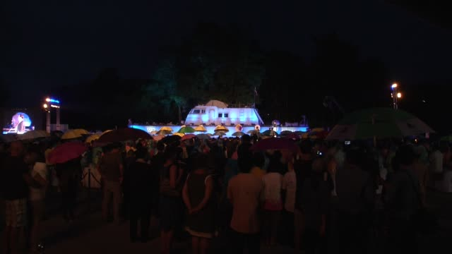 people listen to music while it rains at the 10 years after the tsunami memorial services are held at the police boat 813 tsunami memorial in khao... - police boat stock videos and b-roll footage