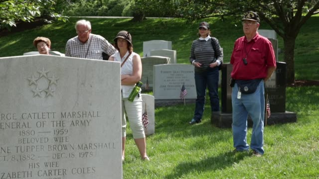 vídeos de stock e filmes b-roll de ls people listening to a tour guide at the gravestone of the most decorated veteran as part of arlington national cemetery 150th anniversary... - cemitério nacional de arlington