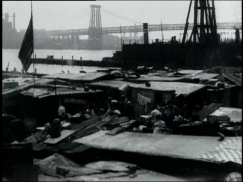 vidéos et rushes de people living in a hooverville shanty town by the river in a shuttered industrial area / usa - la grande dépression