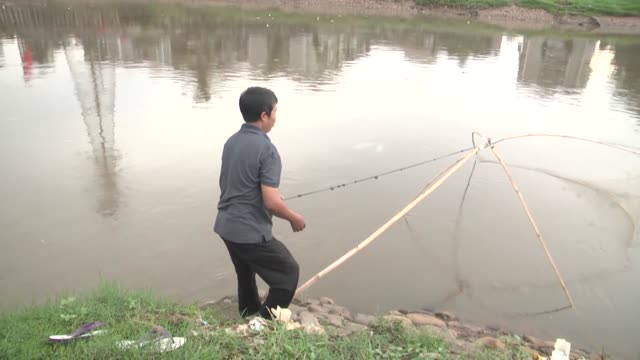 vidéos et rushes de people living on the banks of krukut river desperately try to solve their food problem by fishing by the contaminated river in indonesian capital... - solution
