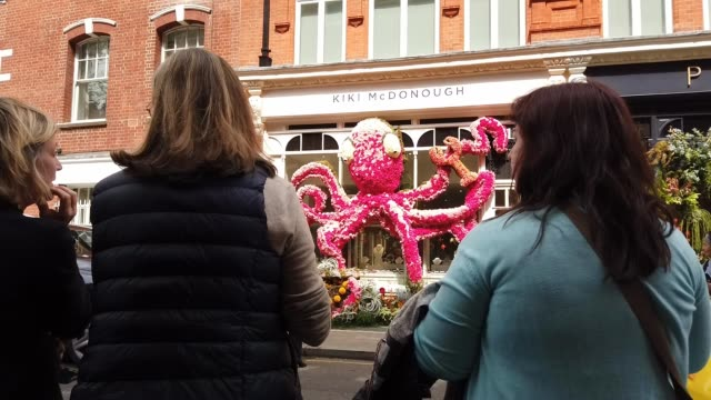 People look at a floral window display in the window of the Kiki McDonough store near Sloane Square as businesses unveil this years creations in...
