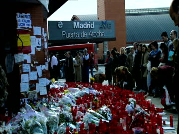 people look at flowers candles and messages of condolences outside madrid train station after al qaeda bombing spain; 2004 - terrorism stock videos & royalty-free footage