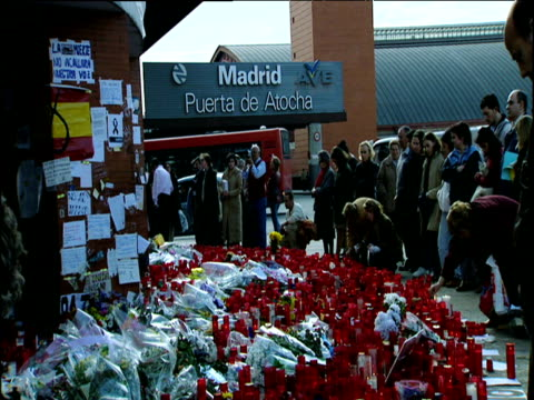 people look at flowers candles and messages of condolences outside madrid train station after al qaeda bombing spain 2004 - 仮設追悼施設点の映像素材/bロール