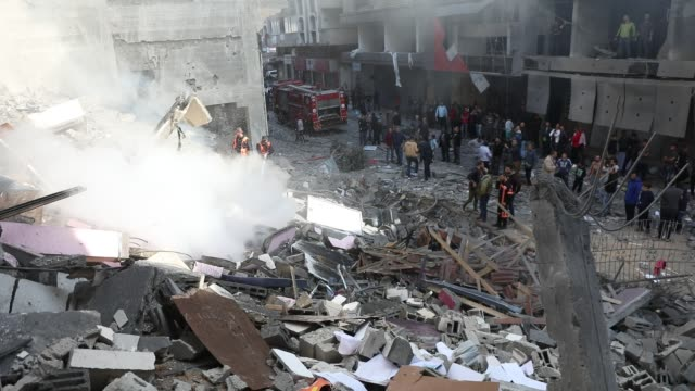 people look at the rubble of a building in gaza city on november 13 after an israeli air strike. - renewed violence in gaza threatened to thwart... - gaza strip stock videos & royalty-free footage