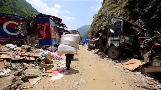 people look for their belongings among the rubble of destroyed buildings as they try to remove the debris and a damaged car is seen on the road in... - tibet autonomous region stock videos & royalty-free footage