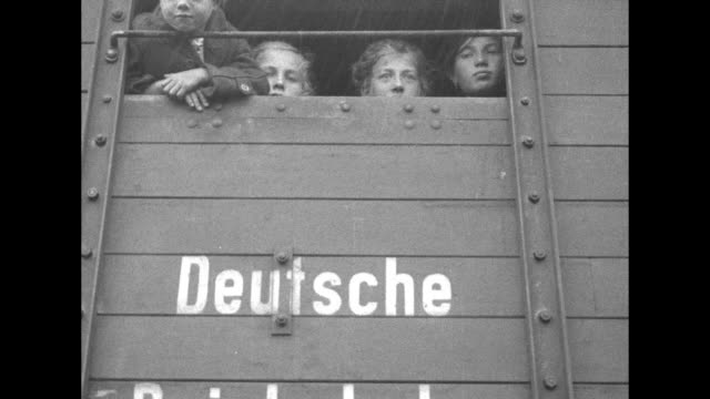 people look from opening in cattle car deutsche and a family in the car with open doors seated in hay with a woman rhythmically moving a pram back... - evacuation stock videos & royalty-free footage