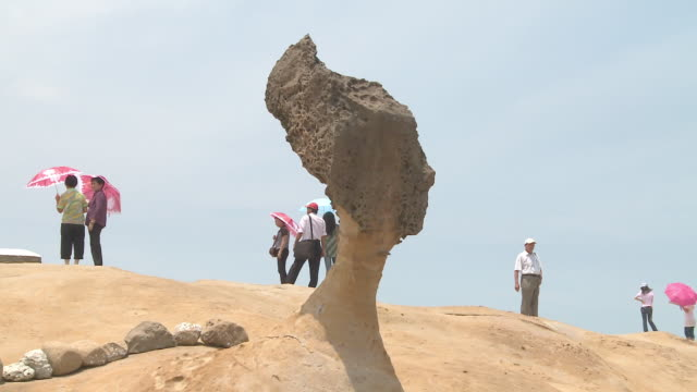 vidéos et rushes de people looking ahead at beach with strange shaped rock in yeliu, taiwan - strate géologique