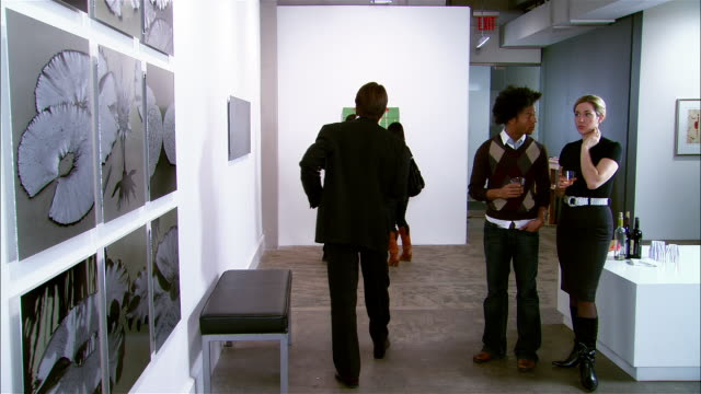 People looking at artwork at gallery opening