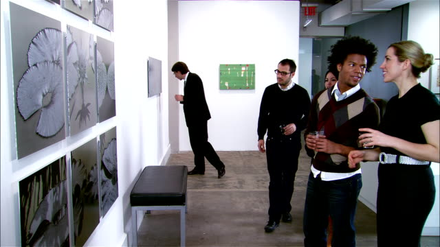 vidéos et rushes de people looking at artwork on wall at gallery opening - musée