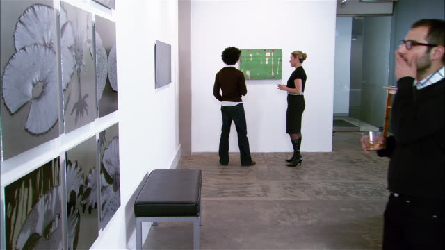 people looking at artwork on wall at gallery opening - museum bildbanksvideor och videomaterial från bakom kulisserna