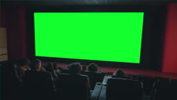 People looking at big green chroma key screen in cinema enjoying film