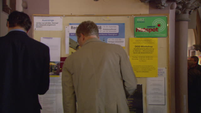 ms people looking at bulletin board announcing upcoming solar conference in marburg / marburg, germany - psa stock videos & royalty-free footage