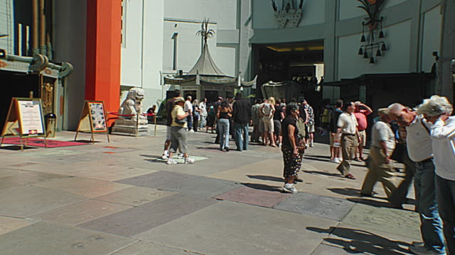 MS T/L People looking at footprints in front of Grauman's Chinese Theatre / Hollywood, California, USA