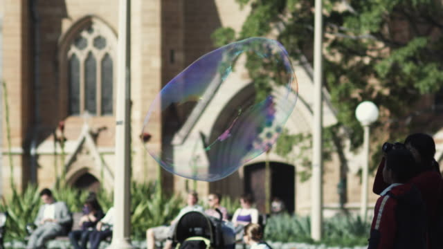 ms pan people looking at large bubble in hyde park, st mary's cathedral in background / sydney, new south wales, australia - 大聖堂点の映像素材/bロール