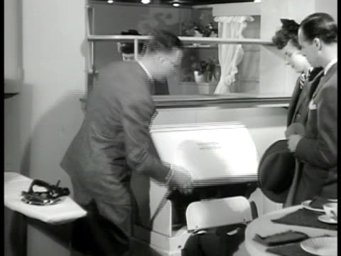 vidéos et rushes de people looking at modern room displays inside wanamaker & co department store, couple looking at kitchen w/ electric mangle next to ironing board.... - fer