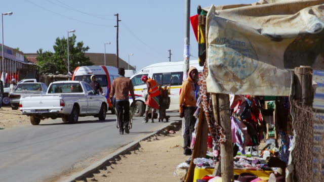 ms people looking at street vendor items along busy town street / diepsloot, south africa - bancarella video stock e b–roll