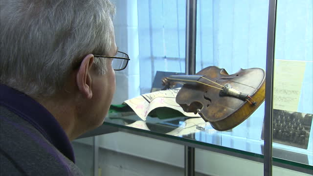 people looking at titanic violin and other memorabilia on display in glass cabinet at auction in wiltshire. titanic violin and memorabilia auction... - wiltshire stock videos & royalty-free footage