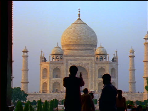 silhouette people looking at + walking away from the taj mahal / agra, india - agra video stock e b–roll