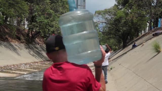 people looking for drinking water in the polluted river that runs through caracas crossing the main highway that runs through the city buckets of... - インフレ点の映像素材/bロール