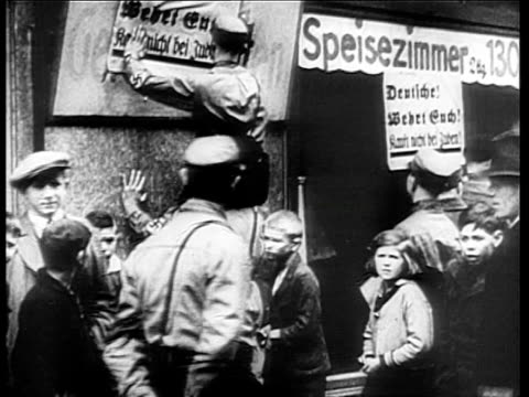 vídeos de stock, filmes e b-roll de people looking into shop with star of david painted on window / nazi brownshirts posting anti-semitic signs as children look on / passing crowd in... - 1933