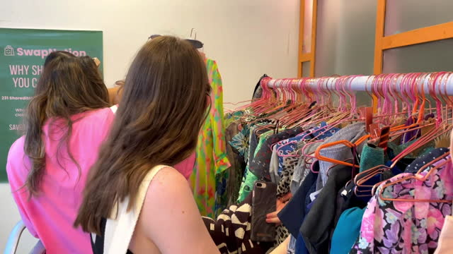 people looking through rails at swap nation, a shop where people swap their unwanted clothes for other people's unwanted clothes, a form of... - other stock videos & royalty-free footage