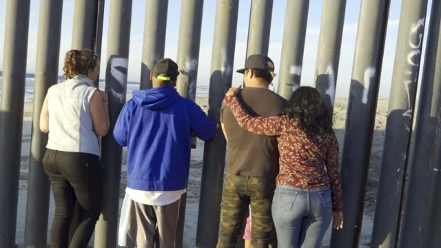 people looking through usmexico border fence from 'las playas de tijuana' mexico side on the us side is 'friendship park' the us border patrol agents... - baja california norte stock videos & royalty-free footage